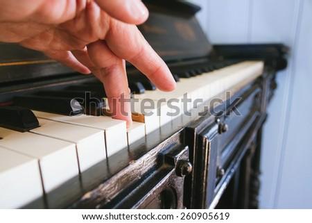 Hand touching the piano - stock photo