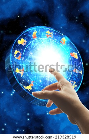 hand touching the zodiac wheel - stock photo