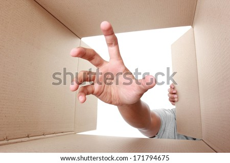 hand trying to grab something inside box