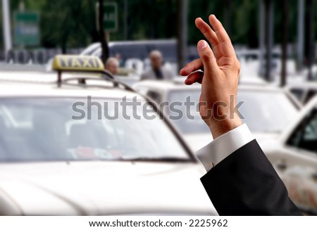 hand trying to pick a taxi - stock photo
