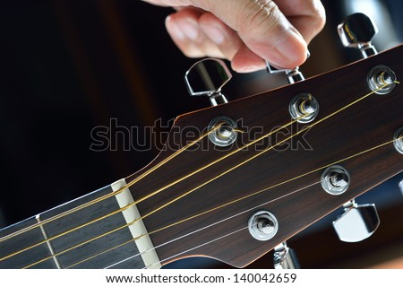 Hand tuning a guitar from headstock - stock photo