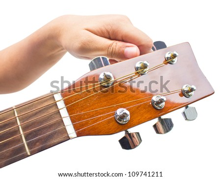 Hand tuning a guitar from headstock isolated on white background. - stock photo