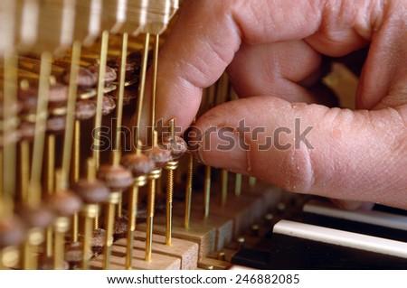 Hand tuning a pipe organ close up - stock photo
