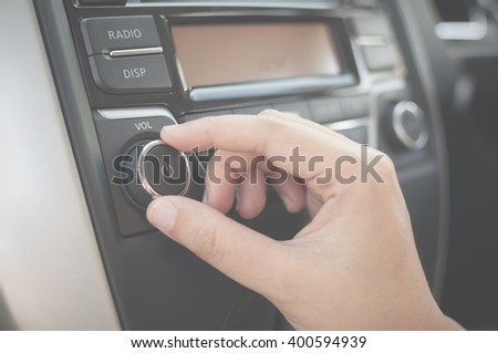 Hand tuning fm radio button in car panel. Retro image processed. - stock photo