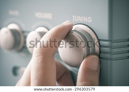 Hand tuning fm radio button. Retro image processed. - stock photo