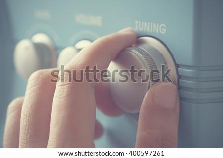 Hand tuning fm radio button. Retro image processed. - stock photo