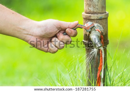 Hand turn off running water from old faucet - stock photo