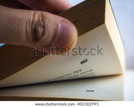 Hand turned over a stack of novel closeup. Focus on page number. - stock photo
