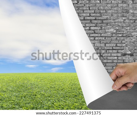 Hand turning old brick wall page revealing nature sky cloud meadow - stock photo