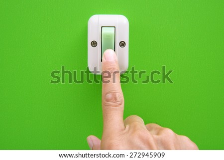 Hand turning on-off the light with wall switch - stock photo