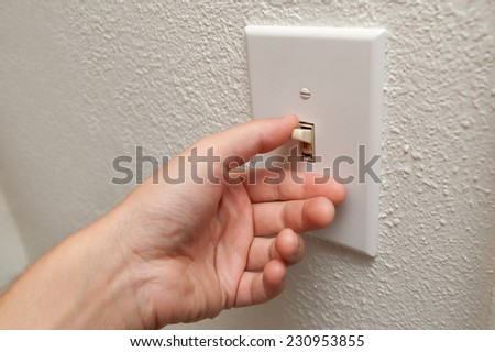 Hand turning wall light switch off - stock photo