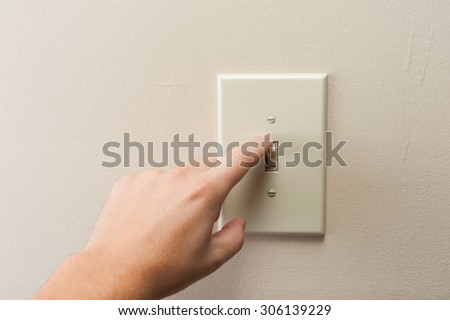 Hand turning wall light switch off. color image in horizontal orientation - stock photo