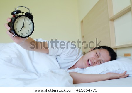 Hand turns off the alarm clock waking up
