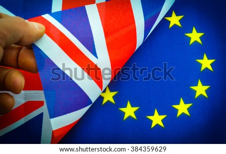 Hand turns UK flag against EU flag with copy space
