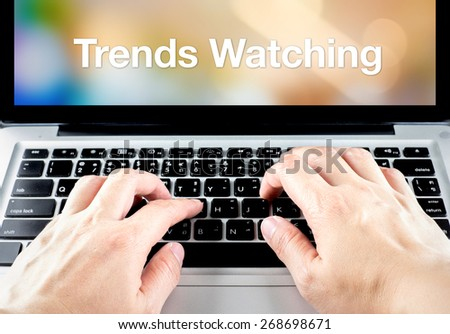 hand type on laptop with trends watching on screen with blur background, online business concept. - stock photo