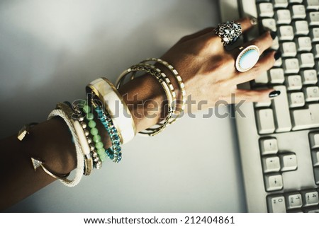 Hand typing on keyboard with bracelets and rings - stock photo