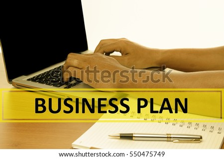 Hand Typing on keyboard with text BUSINESS PLAN