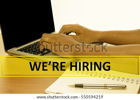 Hand Typing on keyboard with text WERE HIRING