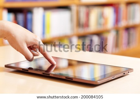 Hand typing on tablet pc in library - stock photo