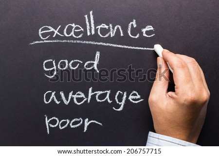 Hand underline Excellence word on audit with chalk