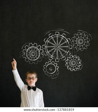 Hand up answer boy dressed up as business man with chalk turning gear cogs or gears on blackboard background - stock photo