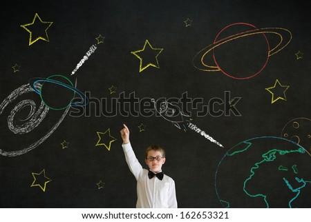 Hand up answer boy dressed up as business man with chalk universe planet solar system on blackboard imagining space travel - stock photo