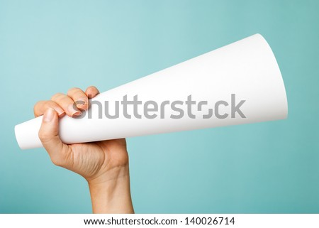 Hand up holding a white blank megaphone on blue background. Native advertising. Influencer marketing concept.