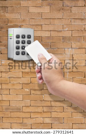 hand use key card  for Security entrance pad on  brick wall - stock photo