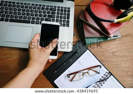 hand use phone and laptop on wooden table - stock photo