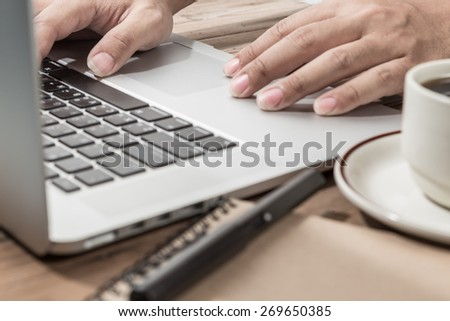 hand using laptop on office desk. Warm tone. - stock photo