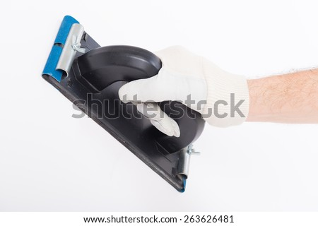 Hand using plastering trowel on white wall - stock photo