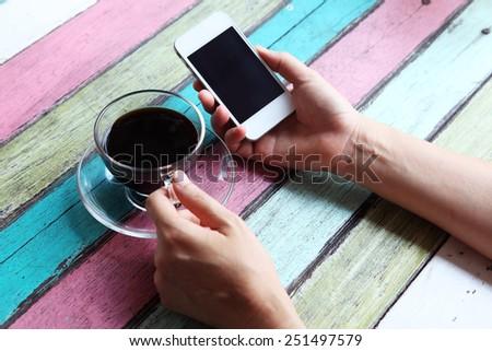 hand using smartphone on coffee table - stock photo