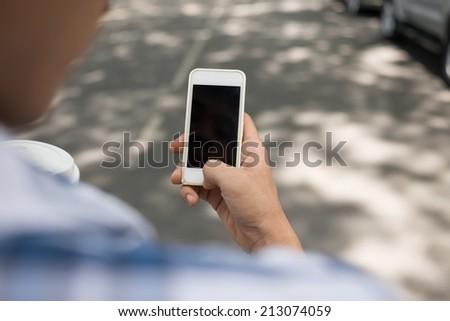 Hand using smartphone outdoors - stock photo