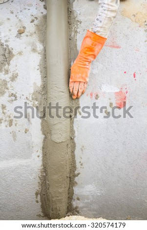 Hand using trowel at construction site - stock photo