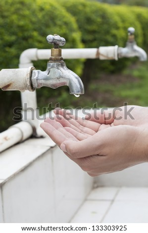 Hand wait for dripping water from old faucet - stock photo