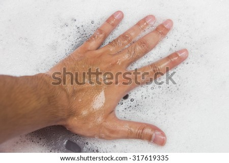Hand washing clothes with soapy water - stock photo
