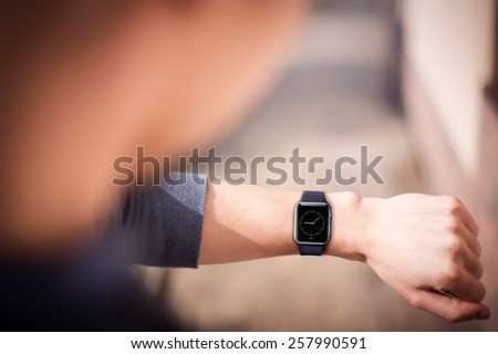 Hand wearing elegant smartwatch with clock app - stock photo