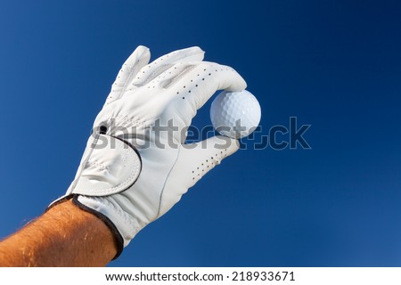 Hand wearing golf glove holding a white golf ball over a deep blue sky. - stock photo