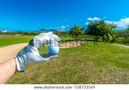 Hand wearing golf glove holding golf ball over beautiful course.