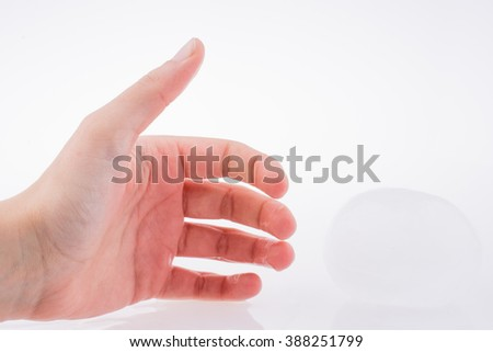 Hand wet and cold by the side of an ice sphere on a white background