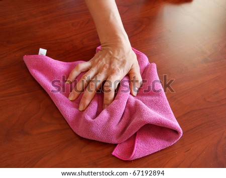 hand wiping wooden surface with pink rag - stock photo