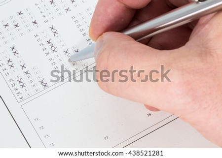 Hand with a ballpen filling out an exam answer sheet - stock photo