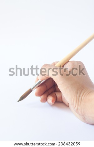 Hand with a brush. Over a grey empty paper, drawing imitation