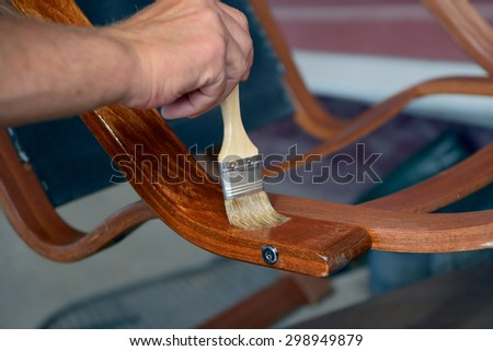 Hand with a brush paints with a varnish a old chair armrest - stock photo