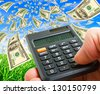 Hand with a calculator on the background of notes flying in the sky. - stock photo