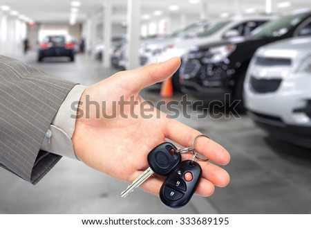 Hand with a car key. Auto dealership and rental concept background. - stock photo