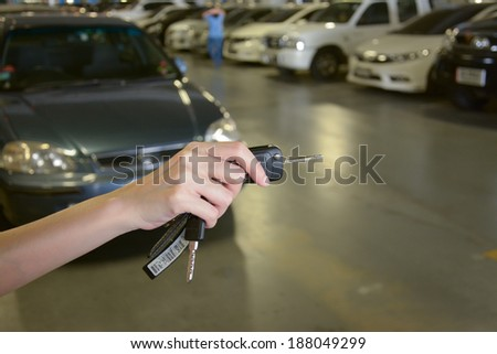 Hand with a Car keys in car park - stock photo