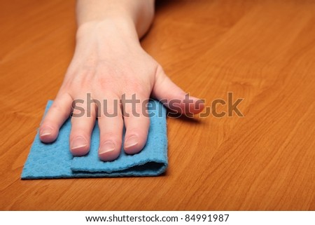 Hand with a cellulose sponge, table - stock photo