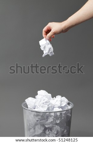 Hand with a crumpled paper and a waste paper basket