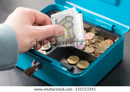hand with a five euro note and a money box - stock photo